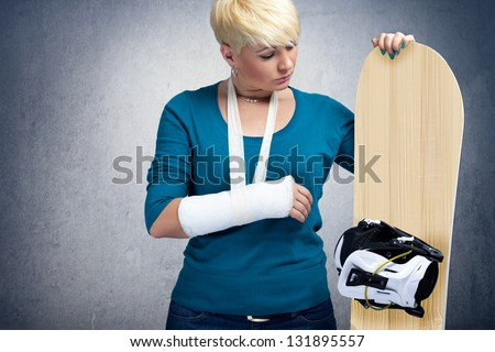 Unhappy snowboarder with  broken arm looking at snowboard - stock photo