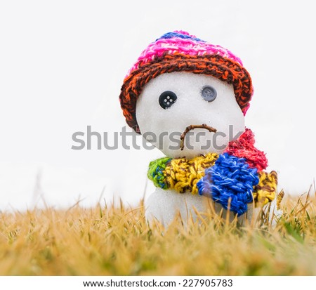 Unhappy snowman melting on green grass with white snow in the background - stock photo