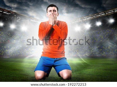 unhappy soccer or football player is down on his knees on stadium - stock photo