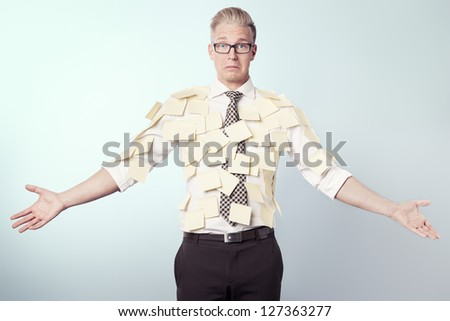 Unhappy stressed businessman with many empty yellow post-it notes with space for text attached to his shirt, isolated. - stock photo