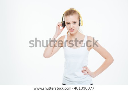 Unhappy stressed young woman listening to music too loud and removing yellow headphones over white background  - stock photo