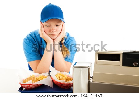 Unhappy teenage girl has a boring job serving fast food.  Isolated on white.   - stock photo