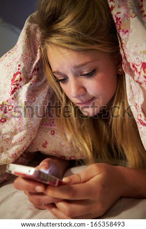 Unhappy Teenage Girl Sending Text Message Whilst Lying In Bed - stock photo