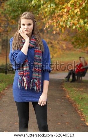 Unhappy Teenage Girl Standing In Autumn Park With Couple On Bench In Background - stock photo