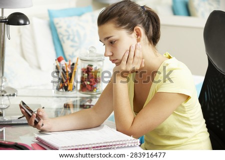 Unhappy Teenage Girl Studying At Desk In Bedroom Looking At Mobile Phone - stock photo