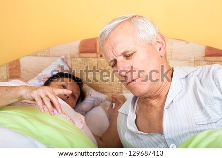 Unhappy tired senior couple in bed waking up. - stock photo