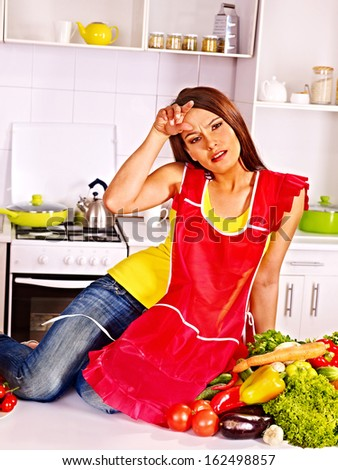 Unhappy tired woman preparing food at kitchen. - stock photo