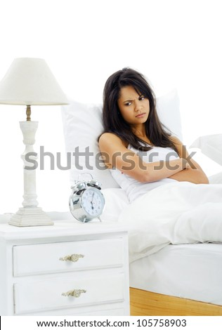 Unhappy woman awake from alarm clock early in the morning is upset about getting out of bed - stock photo