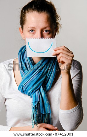unhappy woman is holding paper with drawn smile - stock photo