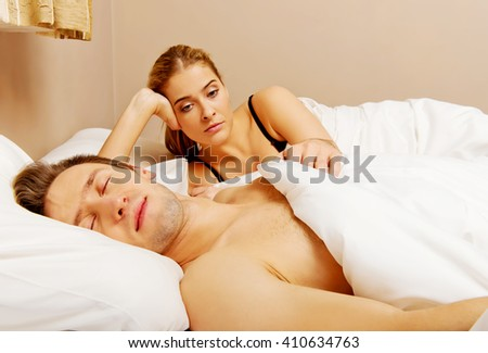 Unhappy woman lying in bed stressed when her husband sleeping - stock photo