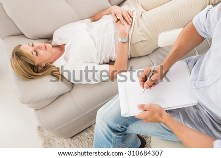 Unhappy woman lying on couch and talking to therapist in the office - stock photo