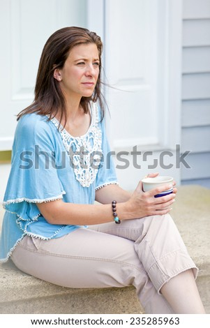 Unhappy woman sitting on door step with a hot drink - stock photo