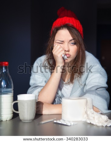 Unhappy woman wearing knitted hat and wrapped in blanket. Tissue paper and pills on the table. Health issue, cold, flue, fever, runny nose concept. - stock photo