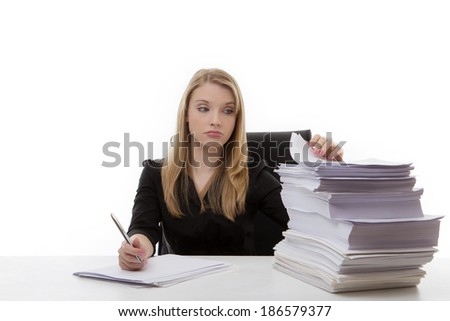 unhappy woman with a large pile of paperwork on her desk to get through - stock photo