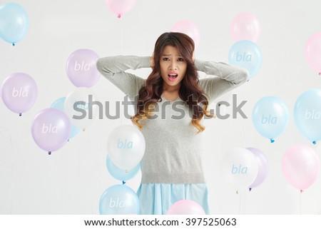 Unhappy woman with bla-bla-bla balloons around her - stock photo