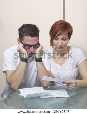 Unhappy young couple in financial trouble at home - stock photo