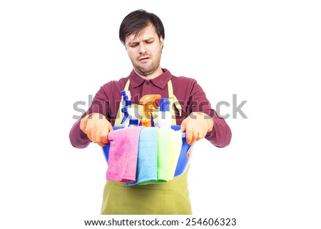Unhappy young man with apron and cleaning equipment over white background - stock photo