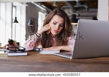 Unhappy young woman studying from cafe - stock photo