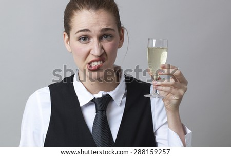 Unhappy young woman wearing uniform of wine waitress holding glass of disappointing white bubbly wine - stock photo