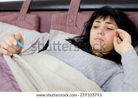 Unhappy young woman with fever in bed - stock photo