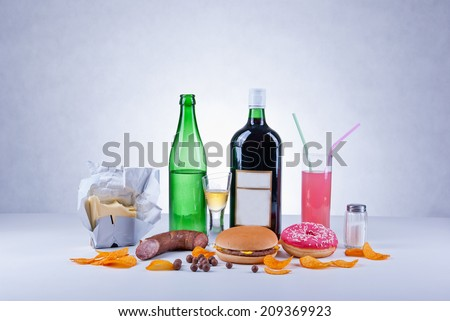 Unhealthy and fat food composition of butter, alcoholic drinks, salt, crisps, hamburger, sausage, donut, candies and colored soda drink.  - stock photo