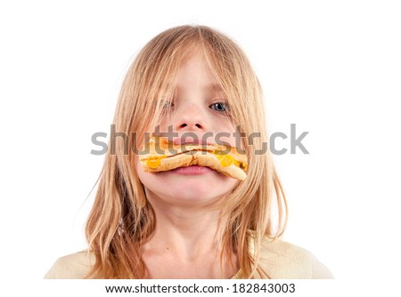 Unhealthy diet for kids - Cute girl with a hamburger in her mouth  - stock photo