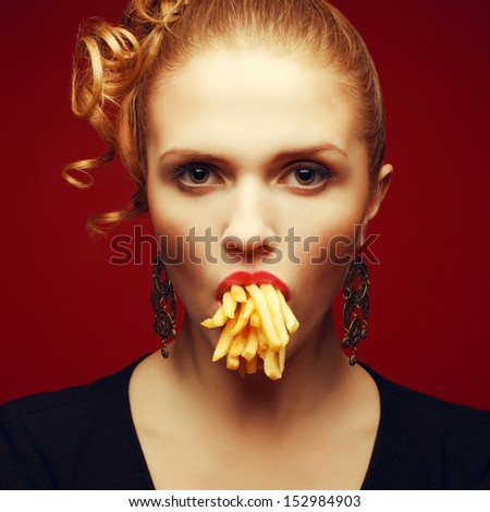 Unhealthy eating. Junk food concept. Arty portrait of fashionable young woman holding (eating) fried potato in her mouth and posing over red background. Close up. Studio shot - stock photo