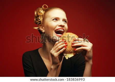 Unhealthy eating. Junk food concept. Guilty pleasure. Happy fashionable hipster girl holding & eating cheeseburger over red background. Perfect hair, skin, make-up & manicure. Copy-space. Studio shot - stock photo