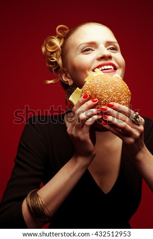 Unhealthy eating. Junk food concept. Guilty pleasure. Happy fashionable hipster girl in black dress holding cheeseburger over red background. Perfect hairdo, skin, make-up & manicure. Studio shot - stock photo