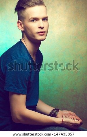 Unhealthy eating. Junk food concept. Portrait of fashionable young man holding popcorn in his hands. Great haircut and healthy skin. Hipster style. Copy-space. Studio shot - stock photo