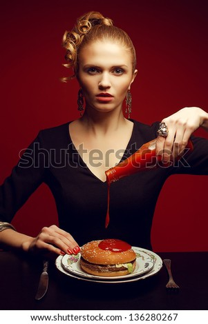 Unhealthy eating. Junk food concept. Portrait of fashionable young woman holding bottle with tomato sauce, pouring it and going to eat burger. Perfect hair, skin, make-up and manicure. Studio shot - stock photo