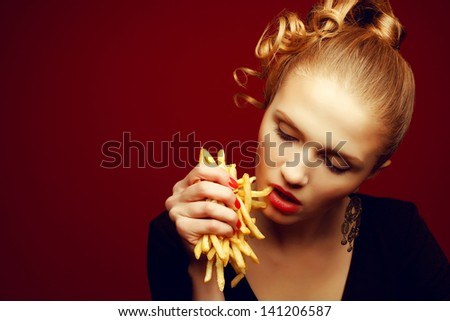 Unhealthy eating. Junk food concept. Portrait of fashionable young woman holding (eating) fried potato (fries, chips), looking down and posing over red background. Close up. Copy-space. Studio shot - stock photo