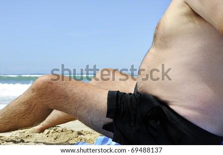 Unhealthy fat man sitting on the beach - stock photo