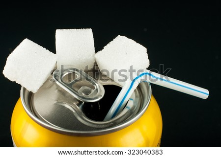 Unhealthy food concept - sugar in carbonated drink. Sugar cubes and canned drink - stock photo