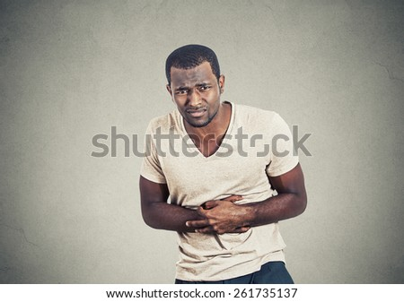 Unhealthy man, doubling over in stomach pain looking sick unwell miserable ill, isolated on grey wall background - stock photo