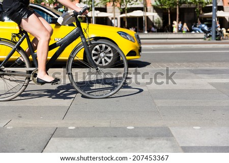 Unidentifiable female person riding a bicycle in the city centre. - stock photo