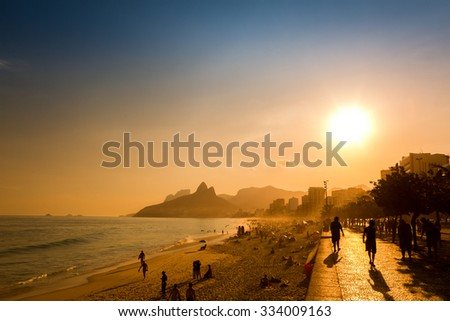 Unidentifiable silhouettes enjoy late afternoon sun rays on Ipanema beach in Rio de Janeiro, Brazil. Ipanema is one of the most expensive places to live in Rio - stock photo