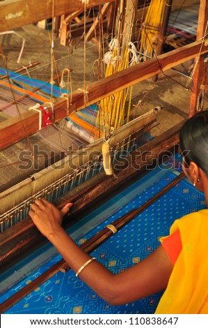 Unidentifiable textile worker weaving Ikkat saree at India - stock photo
