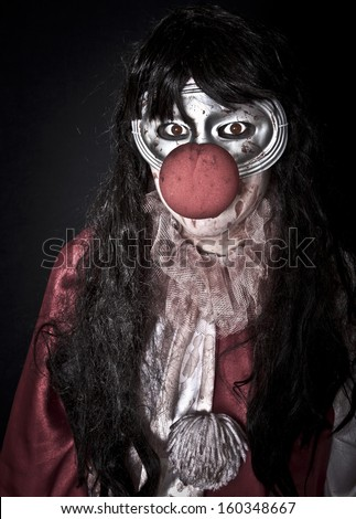 Unidentifiable woman in halloween clown costume with painted eyes - stock photo