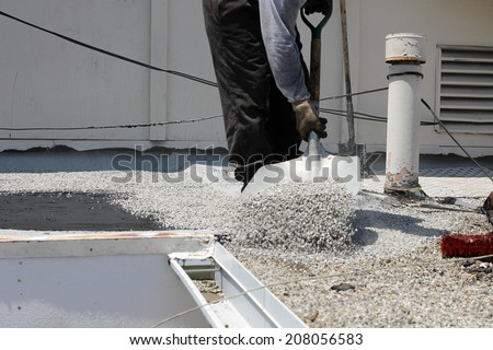 "Unidentifiable workers use ""Hot Tar"" aka ""Hot Mop"" to lay down Molten Tar, Asphalt Sheets and Pea Gravel on a Flat roof on a Hot Summer day in Southern California. Roofs are important on houses - stock photo"