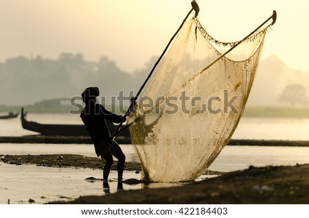 Unidentified Asian fisherman catches fish with lift net, traditional fishing tool at river on sunrise - stock photo