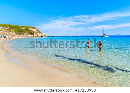 Unidentified attractive young couple of of people in water of beautiful Grande Sperone beach, Corsica island, France - stock photo