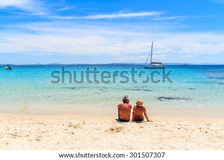 Unidentified couple of people on beautiful sandy Grande Sperone beach, Corsica island, France - stock photo