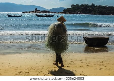 Unidentified fishermen is working on the beach in Nha Trang, Vietnam - stock photo