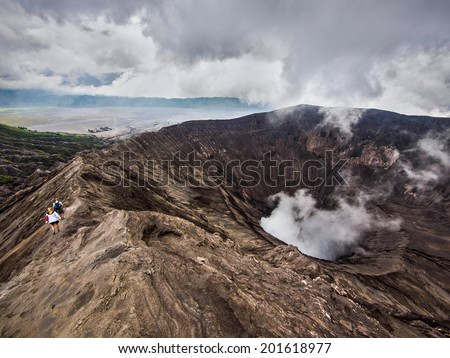 Unidentified hikers walking around the rim of active volcano Gunung Bromo in Java, Indonesia.  - stock photo