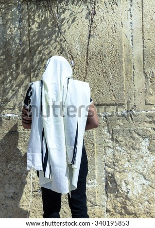 Unidentified jewish worshiper in  tallith and tefillin praying at the Wailing Wall an important jewish religious site. Jerusalem. Israel - stock photo