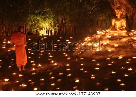 unidentified monk praying to the Buddha - stock photo