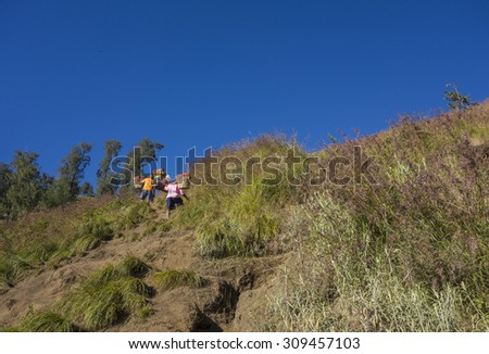 Unidentified mountain porters carry food necessities walks slowly on trekking path on the way to Rinjani Mountain in Lombok, Indonesia. - stock photo