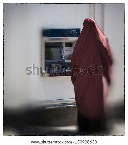 Unidentified muslim woman seen from behind by cashpoint drawing cash. - stock photo