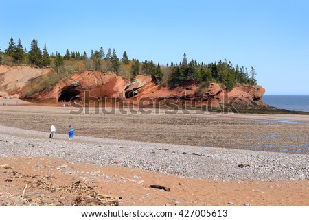 Unidentified people enjoying the rocky beach and caves at low tide in  St. Martins, New Brunswick, in the Maritime Provinces of Canada - stock photo